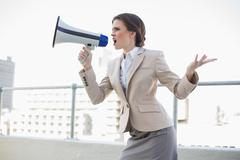 Furious stylish brown haired businesswoman shouting in a megaphone - stock photo