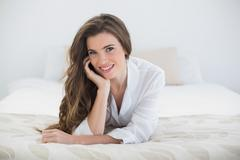 Smiling casual brown haired woman in white pajamas lying on her bed Stock Photos
