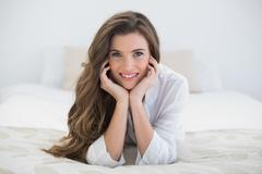 Happy casual brown haired woman in white pajamas lying on her bed Stock Photos