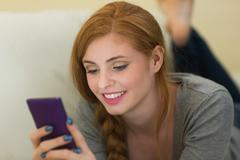 Stock Photo of Pretty redhead lying on the sofa sending a text