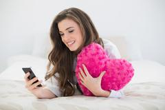 Content casual brown haired woman in white pajamas using her mobile phone - stock photo