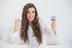 Pleased casual brown haired woman in white pajamas holding a credit card Stock Photos