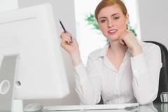Stern businesswoman working at her desk holding pen Stock Photos