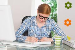 Stock Photo of Redhead writing on notepad at her desk