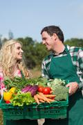 Happy couple presenting vegetables while looking at each other - stock photo