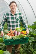 Young man presenting proudly some vegetables - stock photo