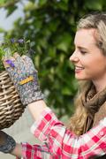 Stock Photo of Pretty blonde fixing a hanging flower basket