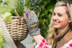 Stock Photo of Smiling woman fixing a hanging flower basket