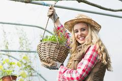Stock Photo of Pretty blonde showing a hanging flower basket