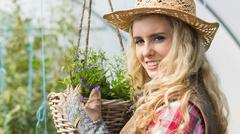 Stock Photo of Smiling blonde touching a hanging flower basket