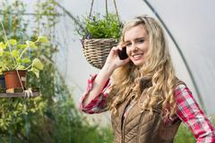 Happy woman mobile phoning in a green house Stock Photos