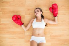 Sporty tired brunette wearing red boxing gloves - stock photo