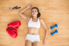 Content sporty brunette lying next to jump rope, red boxing gloves and dumbbells - stock photo