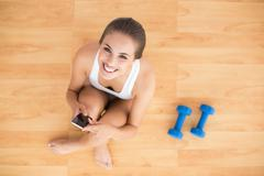 Stock Photo of Smiling sporty brunette holding a mobile phone and sitting next to dumbbells