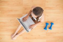 Stock Photo of Sporty brunette using a laptop and sitting next to dumbbells