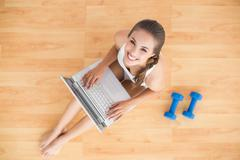 Stock Photo of Smiling sporty brunette using a laptop and sitting next to dumbbells