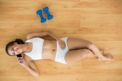 Stock Photo of Smiling sporty brunette using a mobile phone and lying next to dumbbells