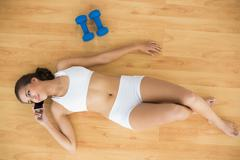 Content sporty brunette using a mobile phone and lying next to dumbbells - stock photo