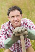 Stock Photo of Smiling man posing with a shovel