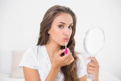 Calm attractive brunette applying lip gloss and holding mirror Stock Photos
