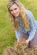 Stock Photo of Pretty blonde feeling yellow straw