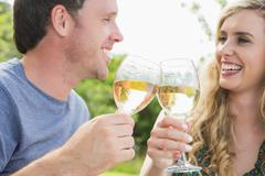 Stock Photo of Cheerful couple toasting with white wine