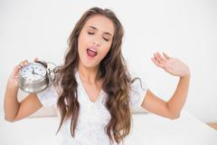 Yawning brunette holding alarm clock - stock photo