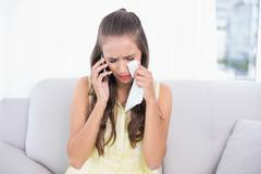 Crying young brunette holding mobile phone and tissue - stock photo