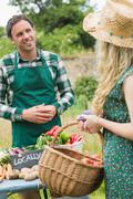 Young farmer selling organic vegetables to pretty blonde - stock photo