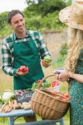 Young handsome farmer selling organic vegetables to pretty blonde - stock photo