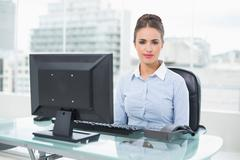 Stock Photo of Calm brunette businesswoman sitting at her desk