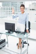 Stock Photo of Smiling brunette businesswoman waving