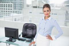Smiling businesswoman standing hand on hips - stock photo