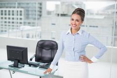 Cheerful brunette businesswoman standing hand on hips - stock photo