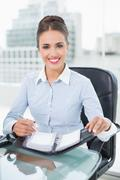 Smiling brunette businesswoman holding a diary Stock Photos