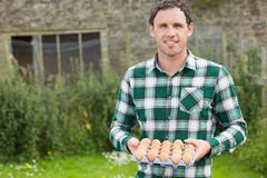Young smiling man holding carton of eggs Stock Photos