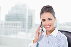 Cheerful brunette businesswoman phoning with smartphone - stock photo
