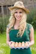 Young smiling blonde woman holding carton of eggs - stock photo