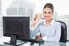 Happy brunette businesswoman holding disposable cup - stock photo