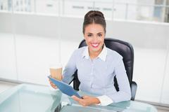 Smiling businesswoman holding tablet and disposable cup - stock photo