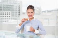 Smiling brunette businesswoman holding mug and cookie - stock photo