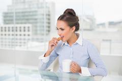 Content brunette businesswoman eating cookie - stock photo