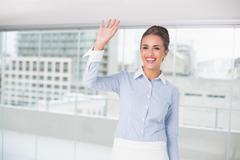 Stock Photo of Smiling brunette businesswoman standing and waving