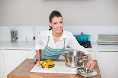 Content pretty woman wearing apron cooking - stock photo