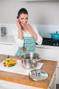 Surprised pretty woman wearing apron having a call - stock photo