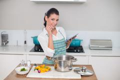 Happy gorgeous woman wearing apron using tablet - stock photo