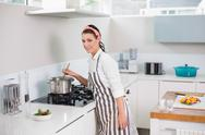 Stock Photo of Smiling pretty woman with apron cooking