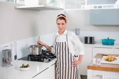 Serious pretty woman with apron cooking - stock photo