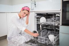 Worried charming woman using dish washer - stock photo