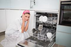 Anxious charming woman sitting next to dish washer - stock photo